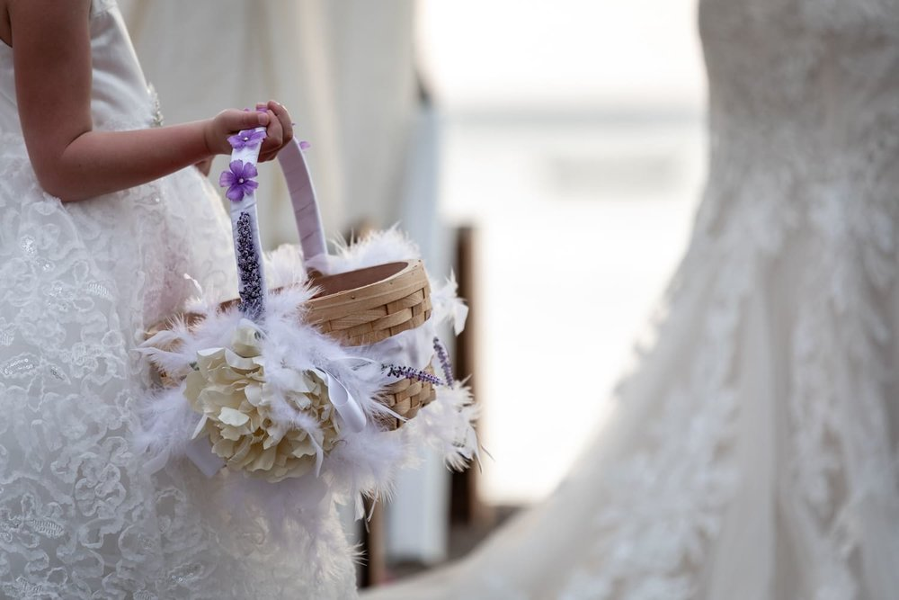 Flower girl holding basket with flower petals next to bride at altar.