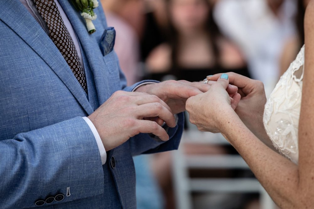 Bride and groom exchanging rings at beach wedding ceremony.