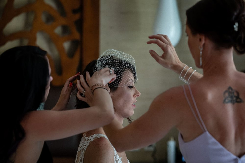 Bridesmaids help bride put on bird cage wedding veil.