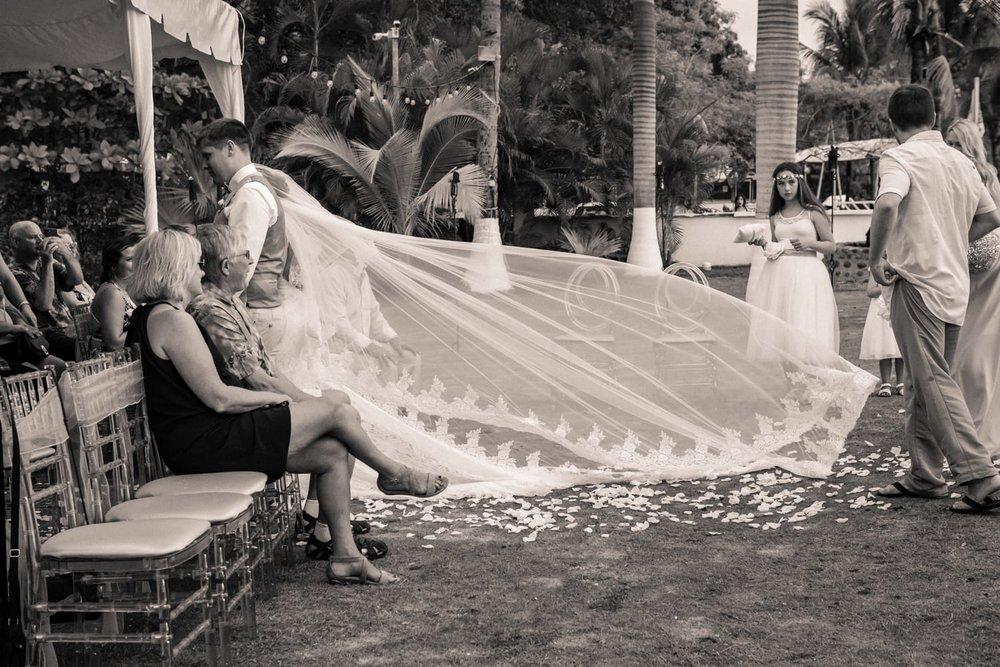 Bridesmaid holds long white wedding veil as bride walks down aisle.