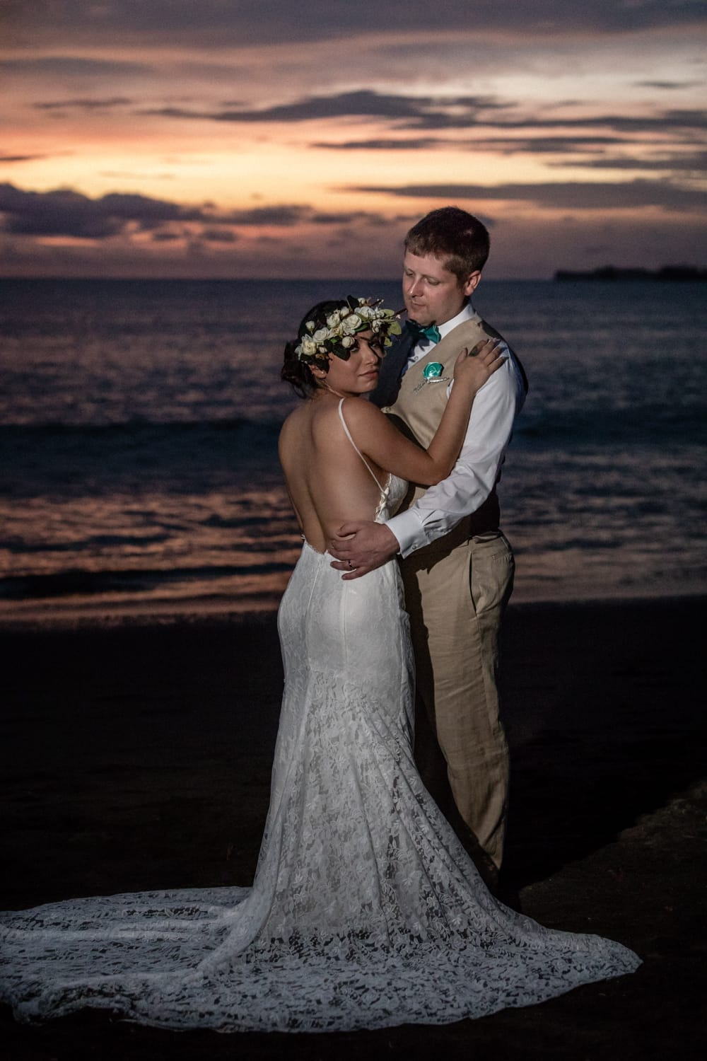 Bride wearing amazing wedding dress poses for portrait with groom on beach at  sunset.