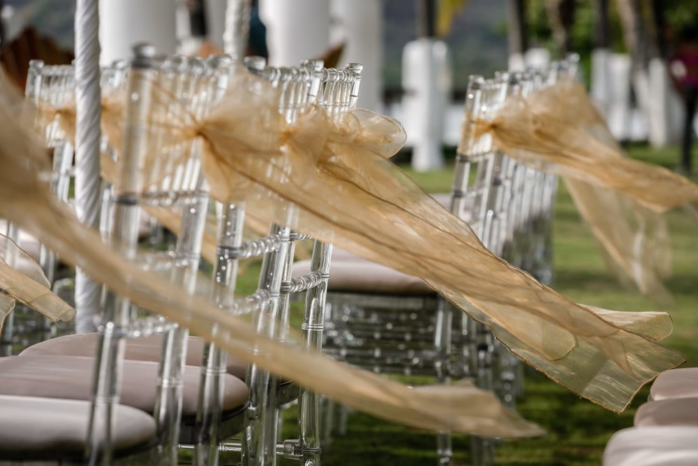 Chairs for wedding guests decorated with gold ribbons.