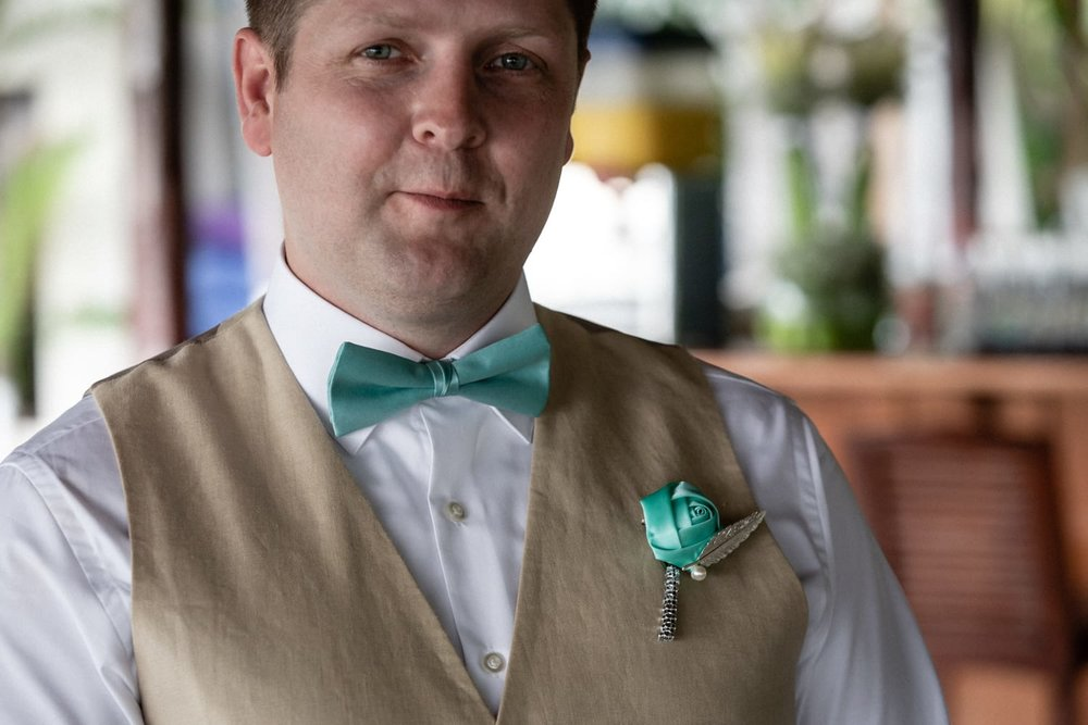 Groom wearing turquoise boutonniere that matches bowtie.