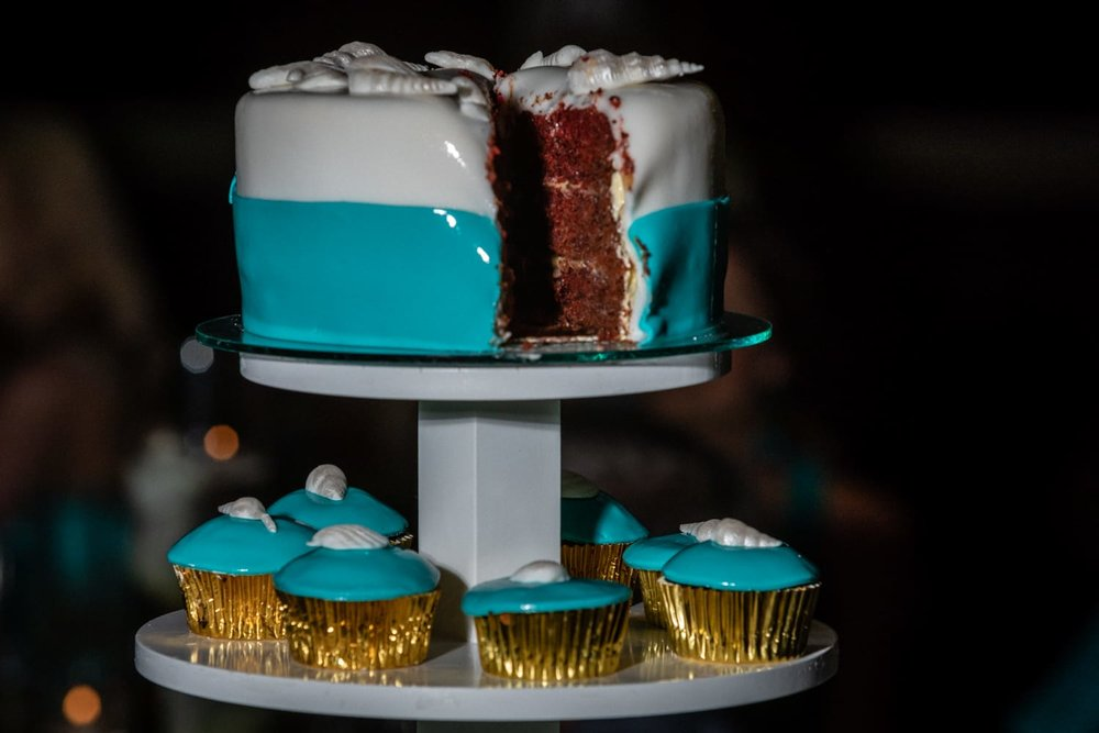 Wedding day cake and cupcakes with beach-themed colors.