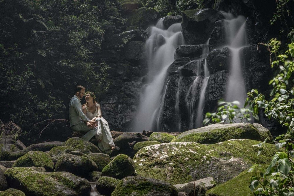 Bride and groom sit on log in front of waterfall in rainforest.