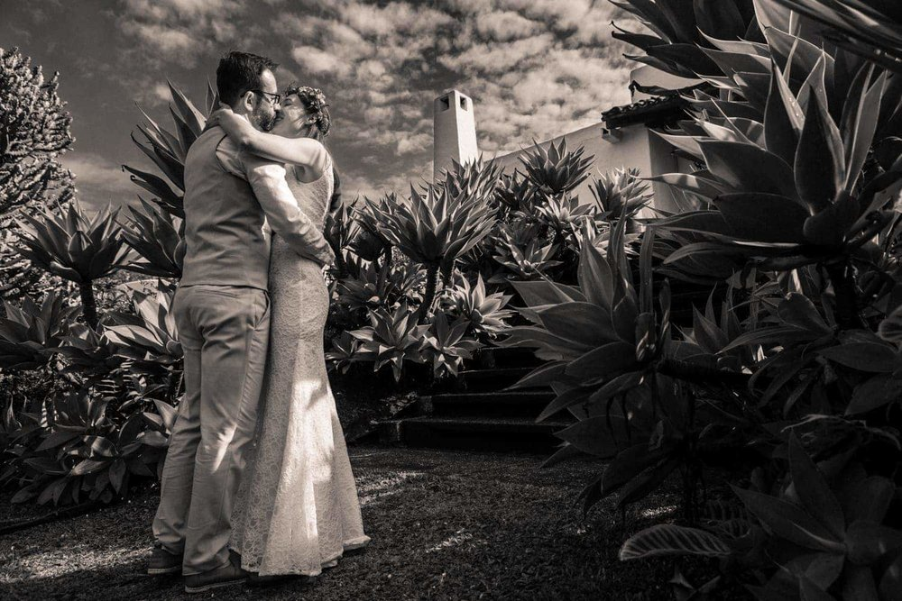 Photo of bride and groom hugging in tropical garden.