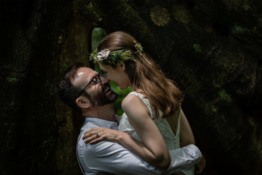 Just married couple pose for photo in front of large tree in rainforest.
