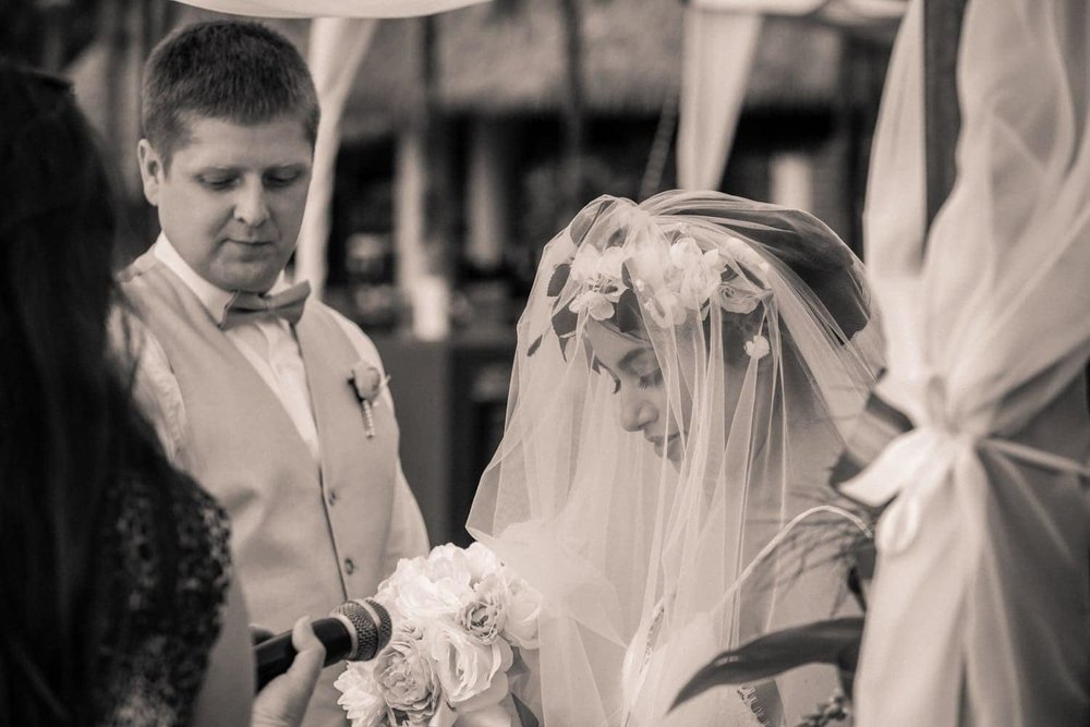 Bride wearing beautiful full veil during beach wedding ceremony.