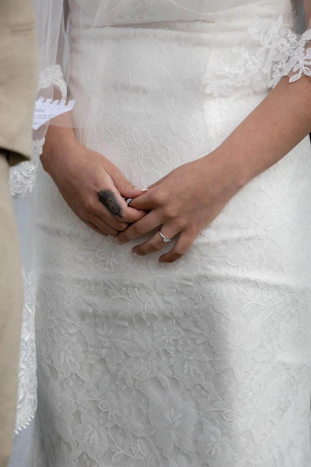 Bride holding grooms wedding ring in hand during wedding ceremony.