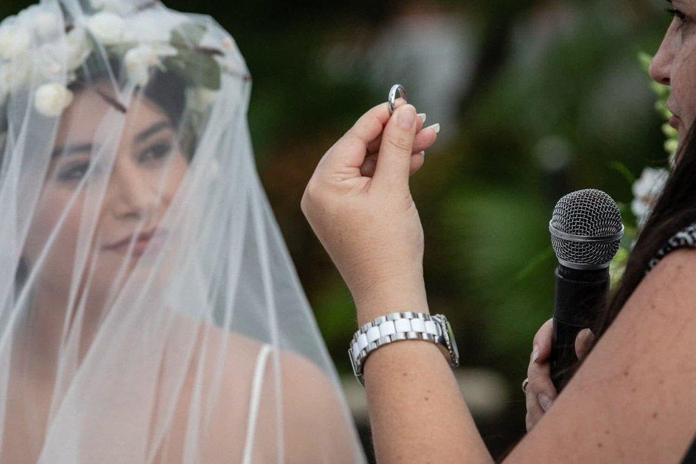 Bride wearing gorgeous full wedding veil looks at fiancé's wedding band.