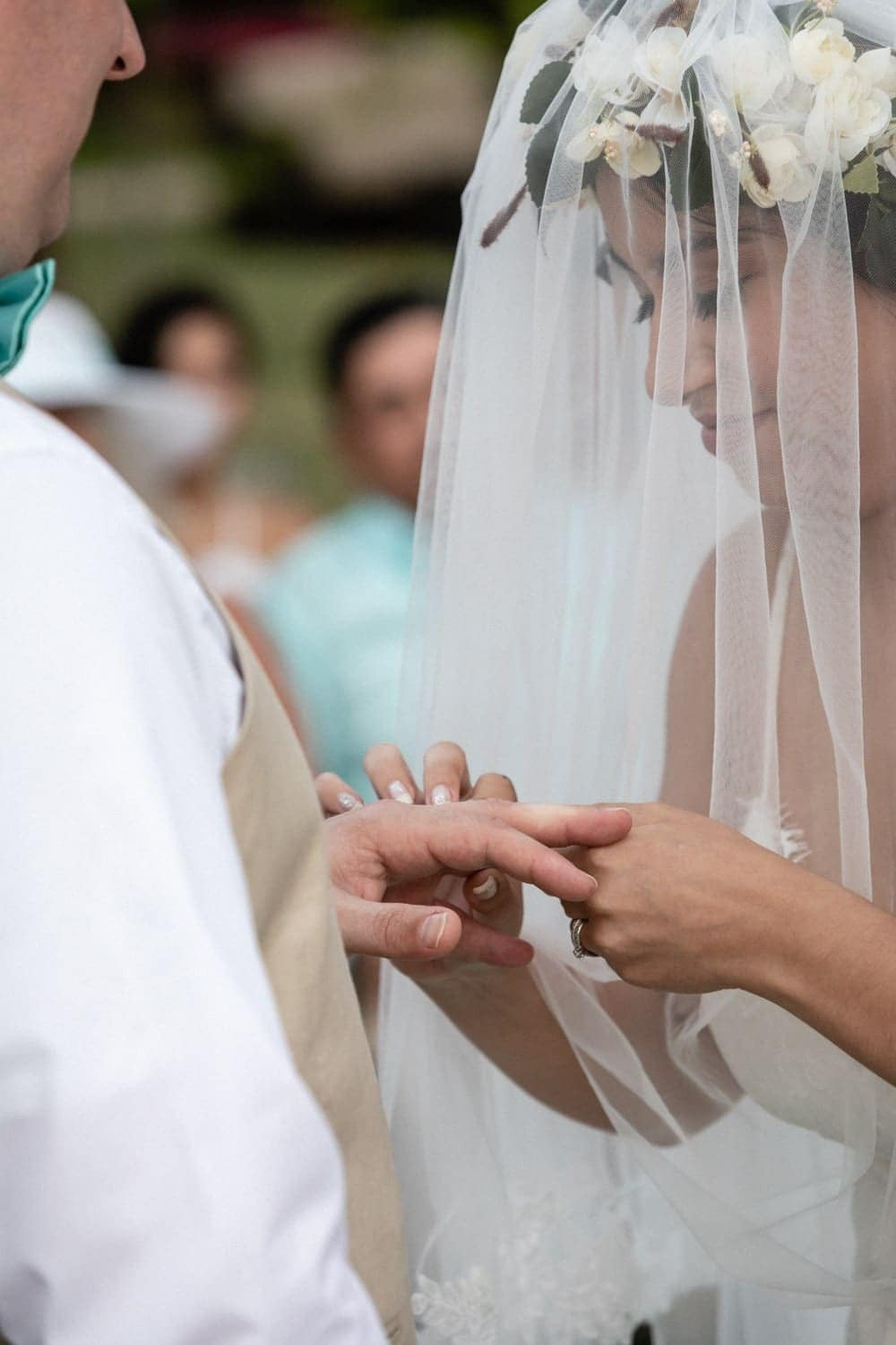 Groom watches bride in beautiful wedding dress put ring on his finger.