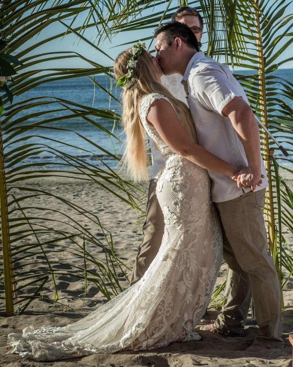 Bride and groom kiss after saying vows during breach wedding ceremony in Tamarindo.