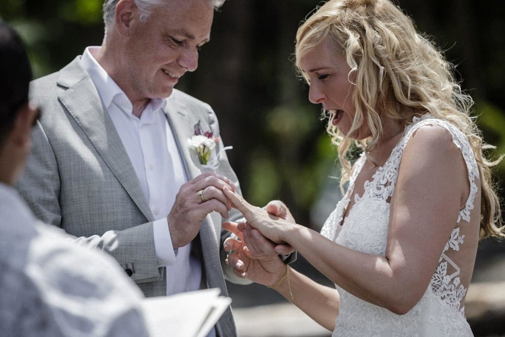 Groom puts wedding band on emotional bride's finger during beach wedding ceremony.