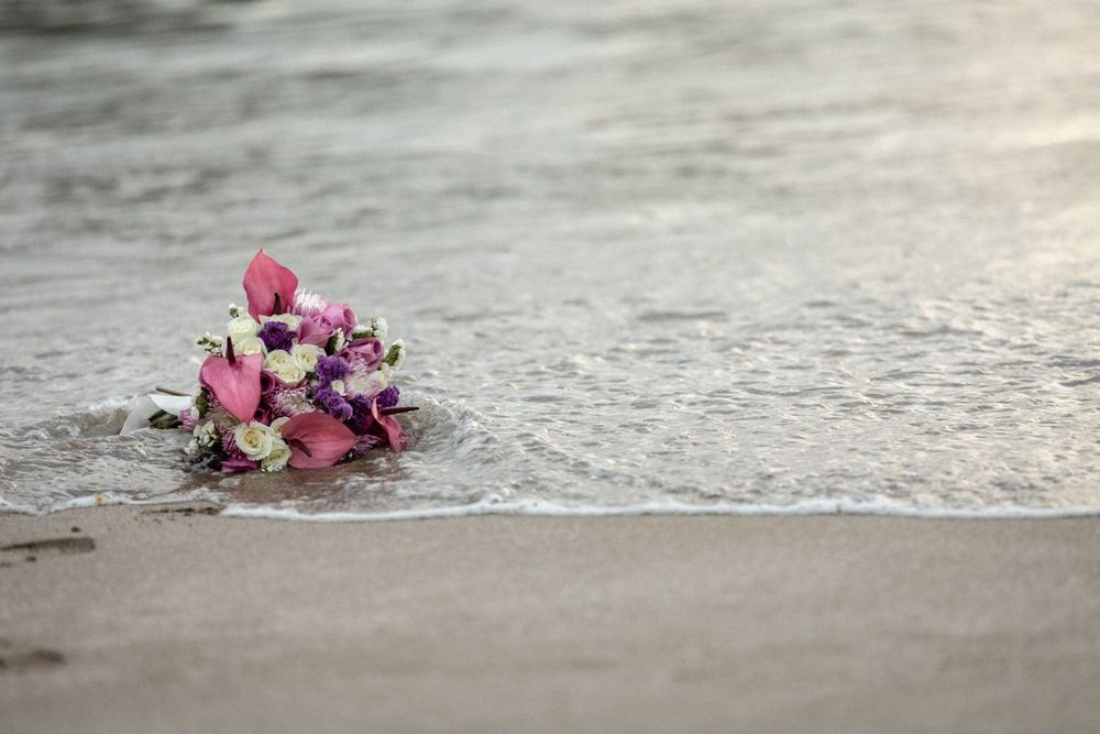 Amazing bridal floral bouquet on beach sand as wave comes in.