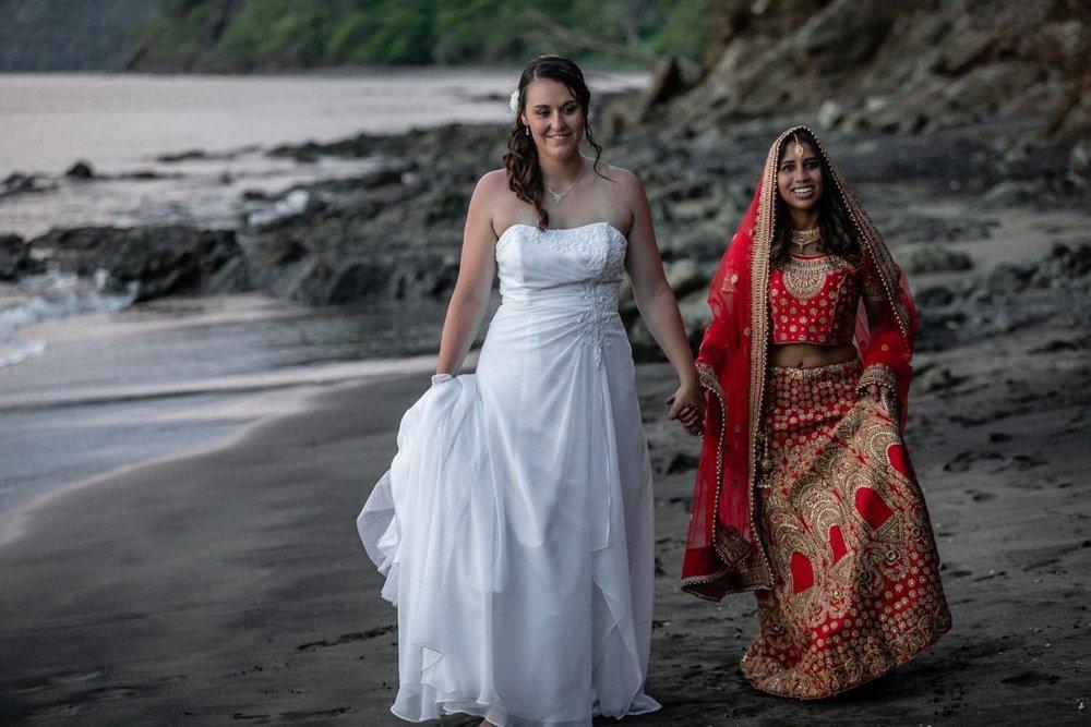 Brides holding hands walk on beach at sunset at Secrets Papagayo.