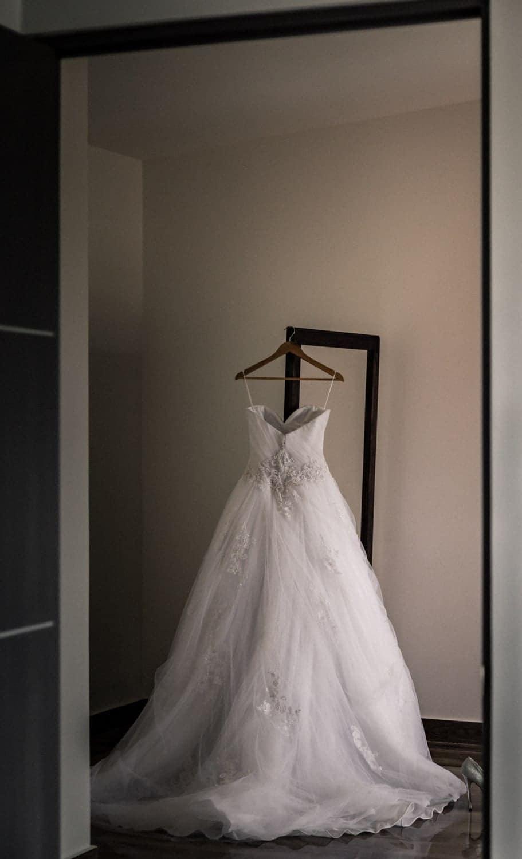 Beautiful wedding dress hanging on mirror during bridal preparation.