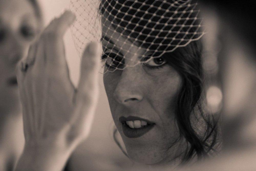 Bridesmaids help bride put on birdcage veil in Dreams Las Mareas suite.