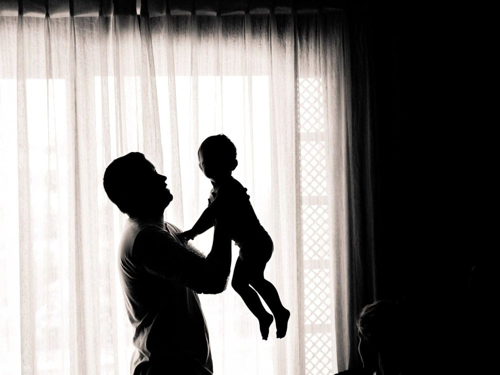 Silhouette of groomsman holding baby in front of window in bridal suite.