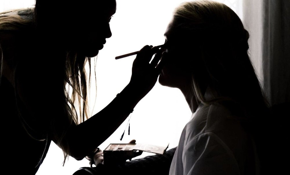 Silhouette of bride having wedding day makeup put on.