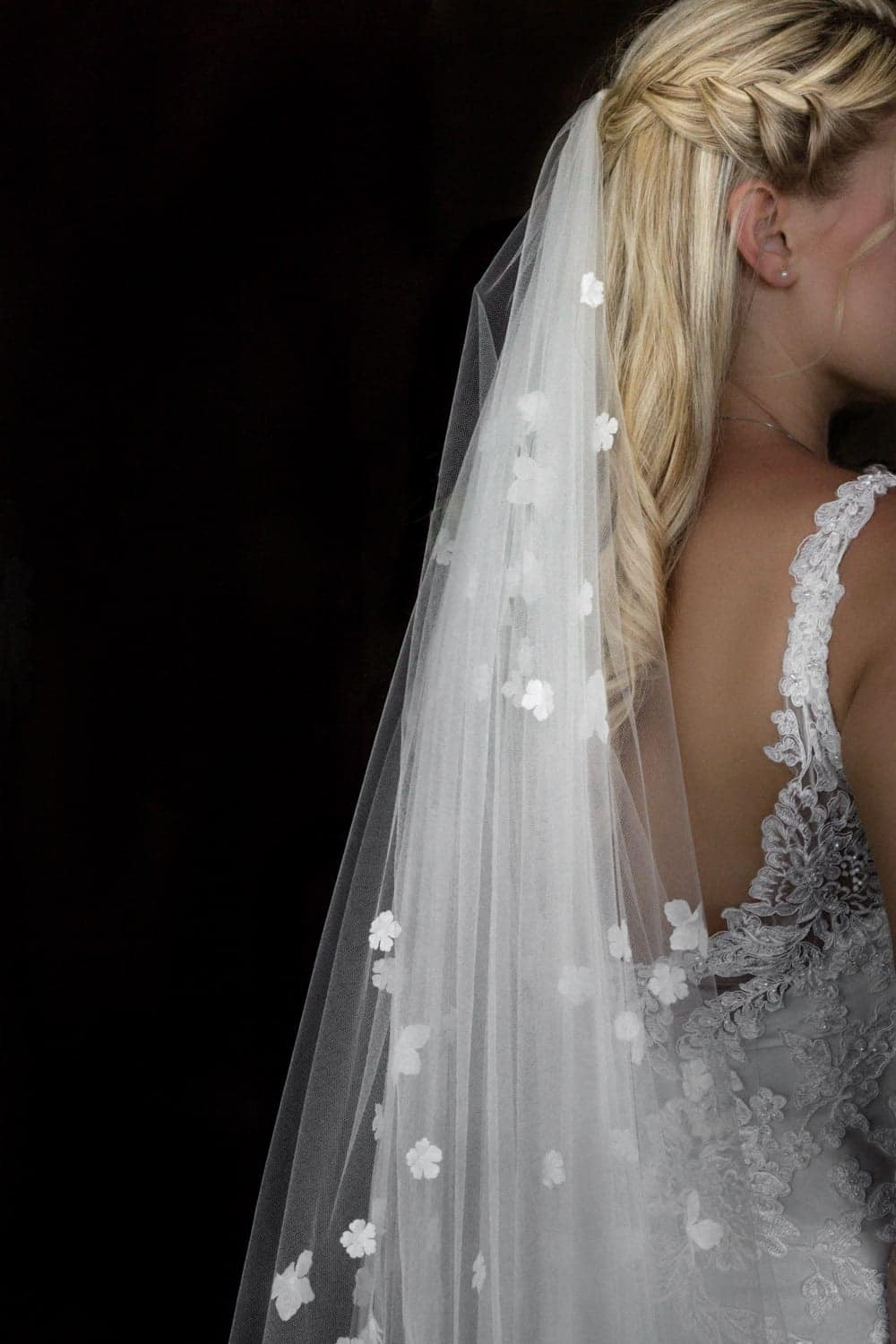 Bride with beautifully breaded blonde hair wearing white wedding veil.