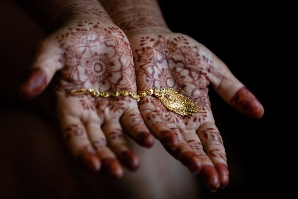 Bride with henna-decorated hands holds jewelry for wedding.