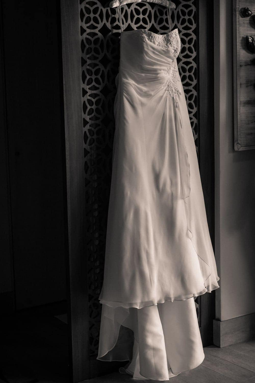 White wedding dress hangs from ornate wood wall in bridal suite at Secrets Papagayo.