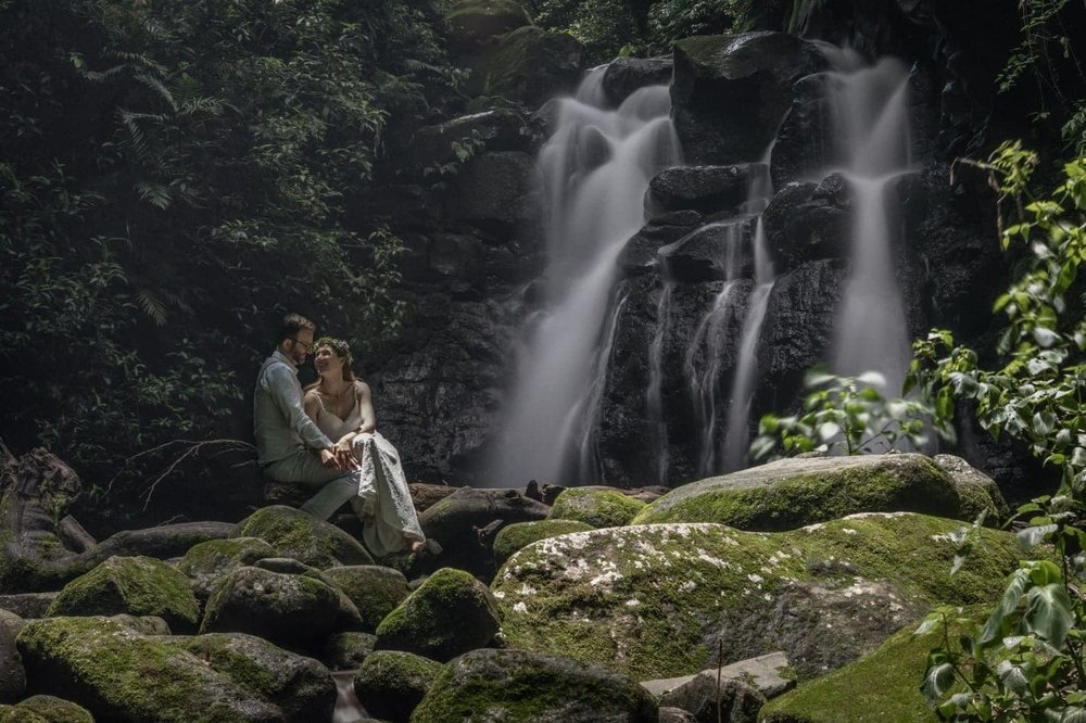 Wedding photo of bride and groom at rainforest waterfall.