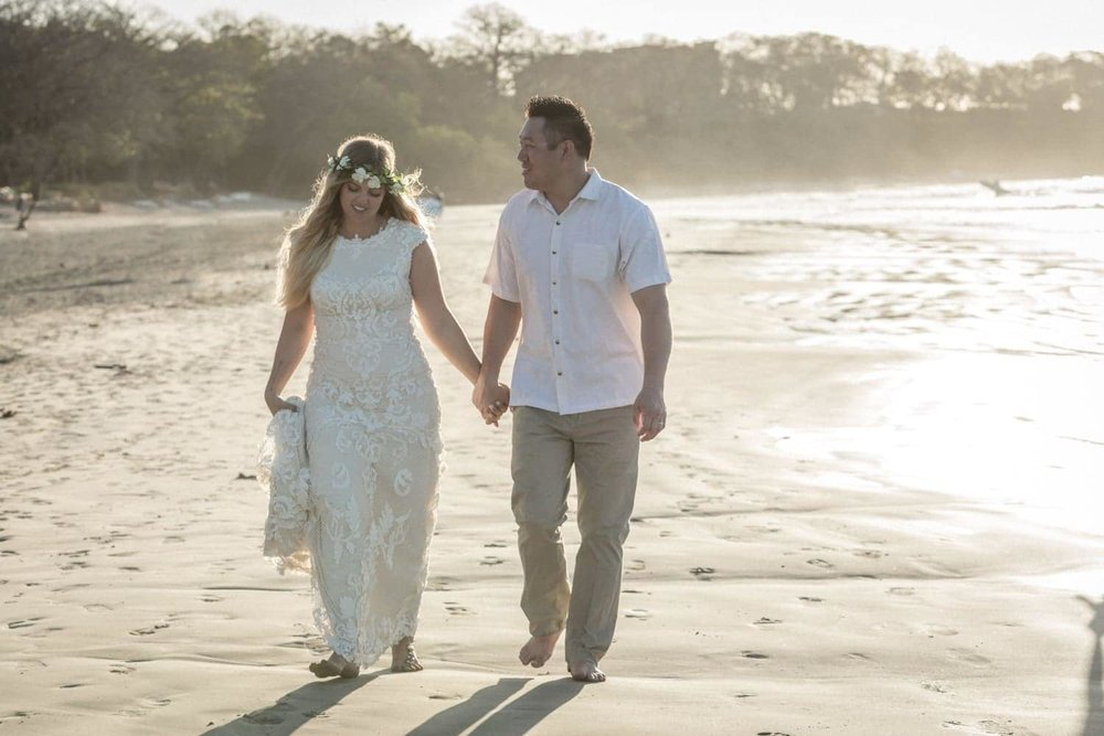 After getting married on beach, lovely couple takes a sunset stroll.