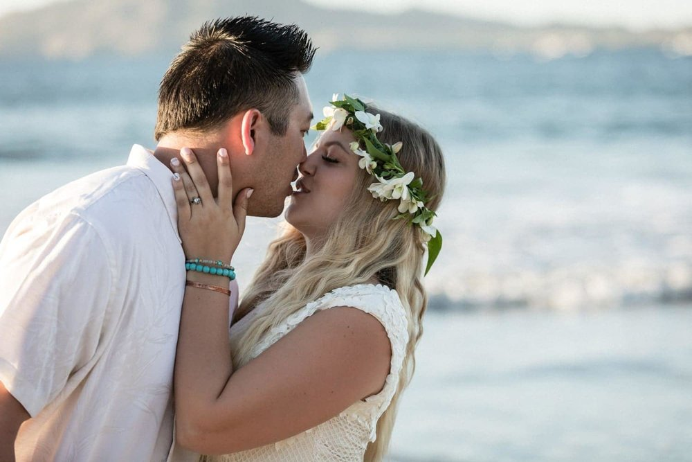 Couple share passionate kiss on beach after tying the knot at Langosta Beach Club.