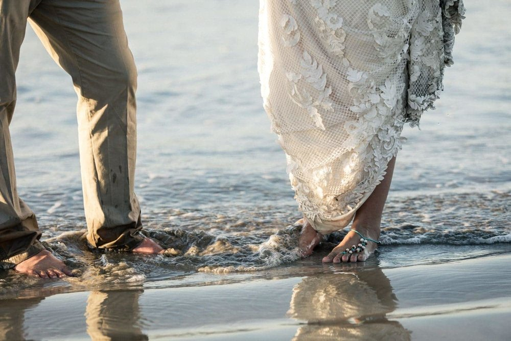 Couple how just tied the knot stand in waves on beach in Tamarindo.