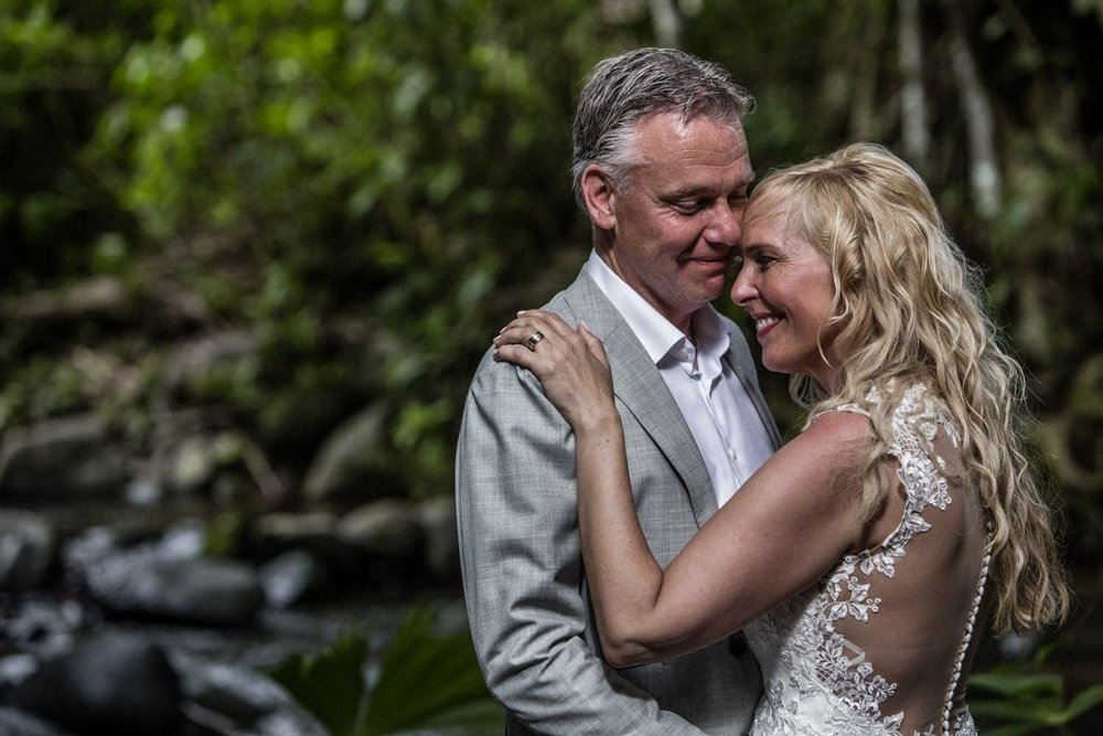 Romantic photo of just married couple standing by river in tropical garden.