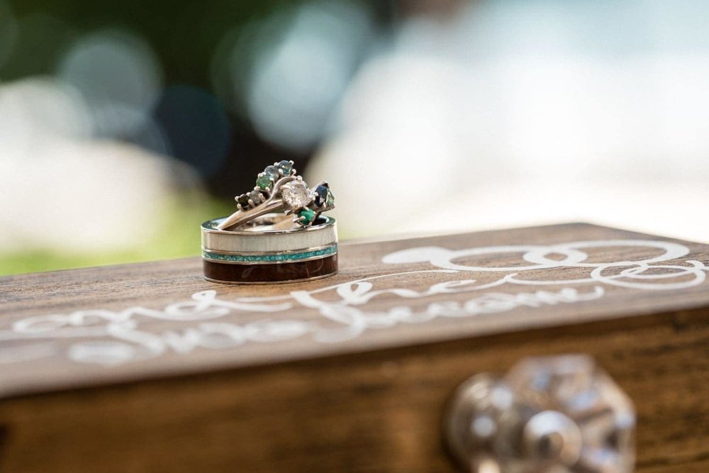 Wedding bands on ring box with beach in Tamarindo in background.