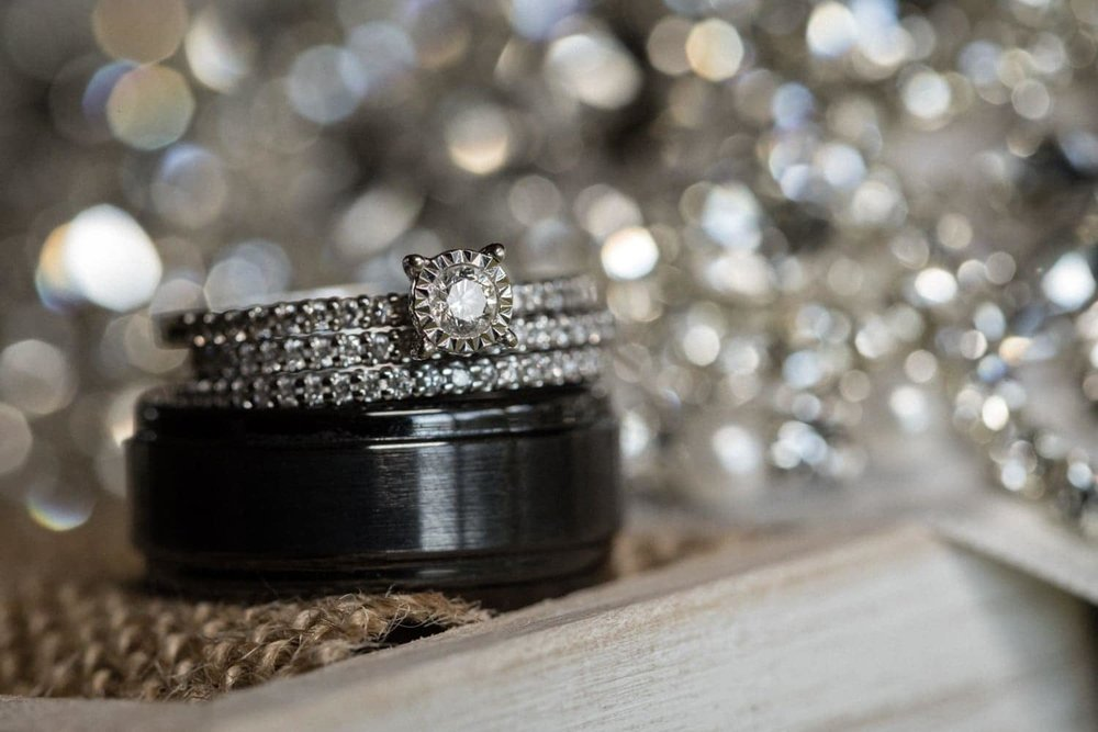 Wedding bands sitting on jewelry box with glittery background.