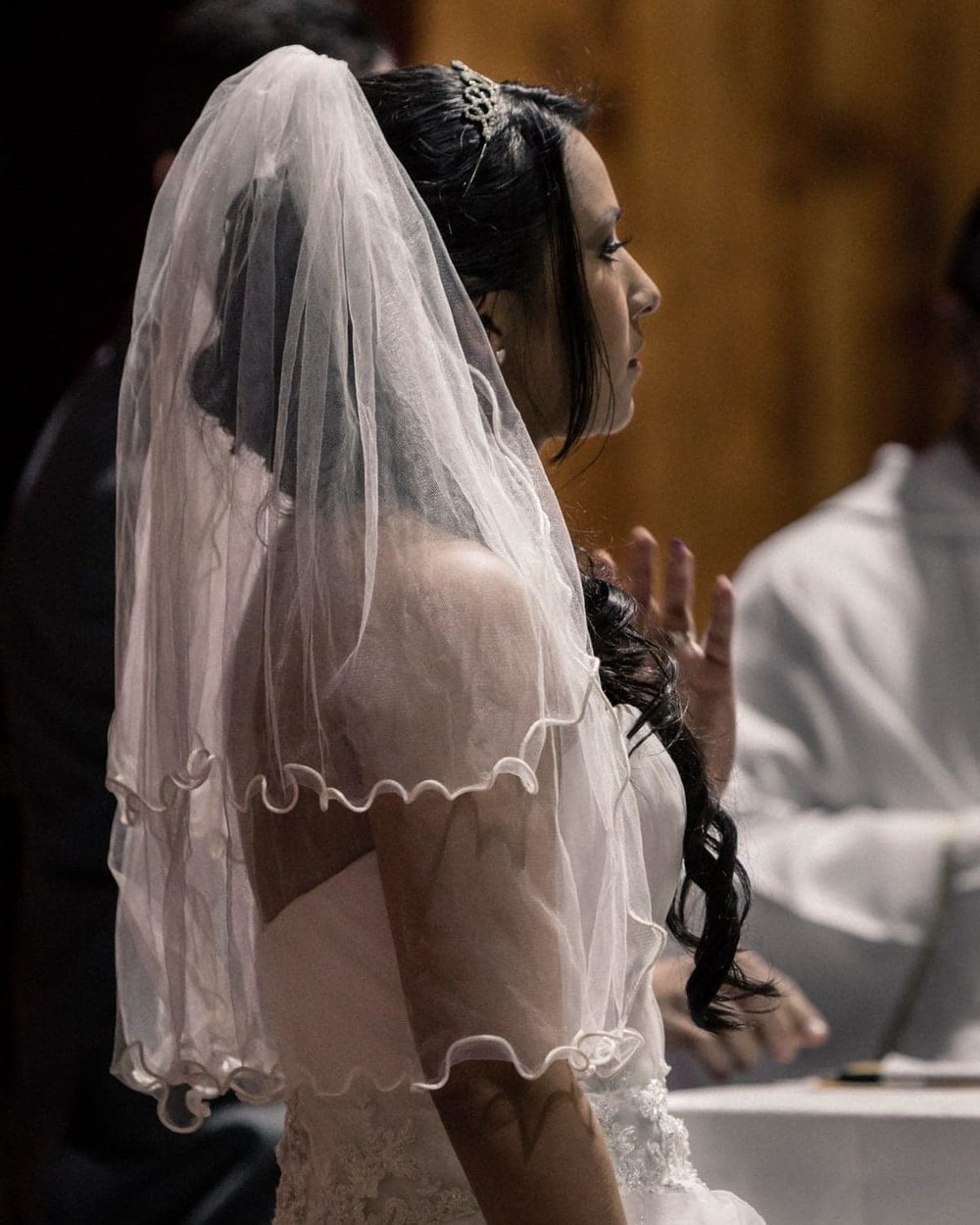 Bride wearing white veil stands patiently during signing ceremony.