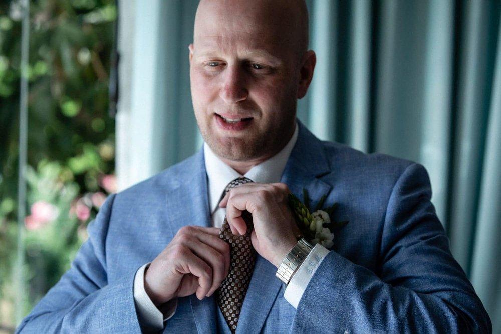 Groom preparing for wedding ceremony adjust his tie.