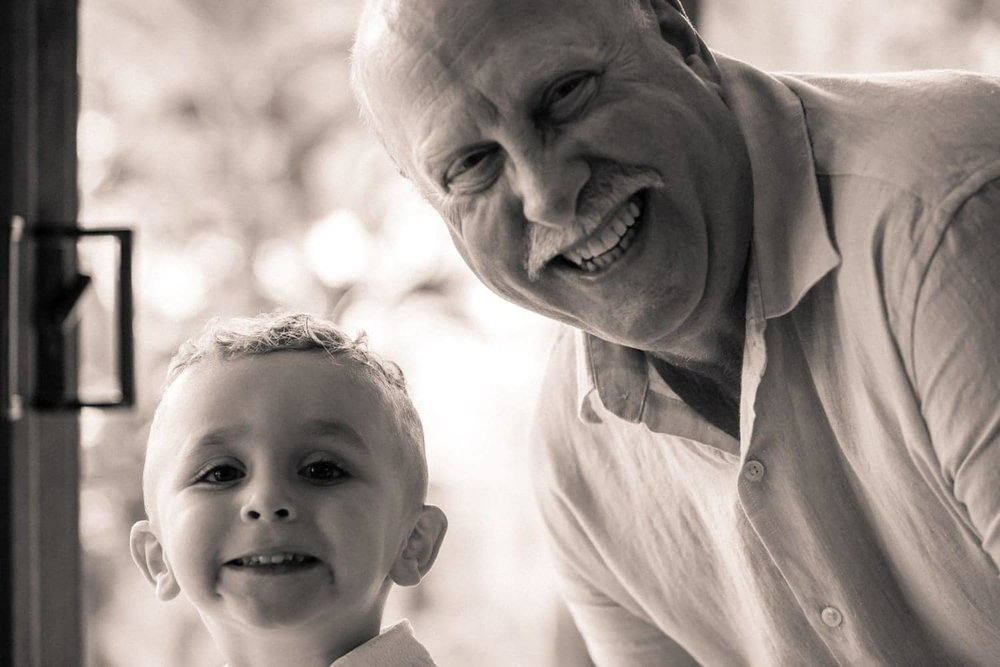 Grandfather and grandson pose for a photo while preparing for wedding.