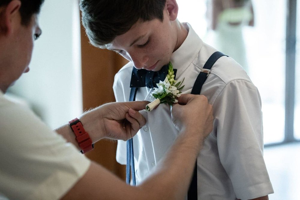 Wedding page getting help putting on boutonniere.