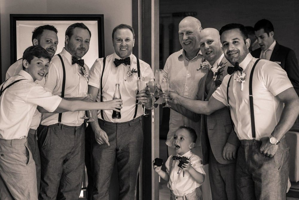 Groomsmen and ring bearer have a toast before heading to beach for ceremony.
