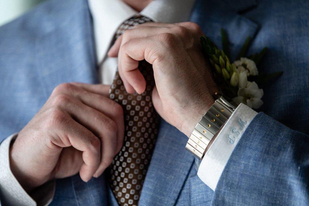 Groom adjusts his tie while preparing for wedding at Dreams Las Mareas.