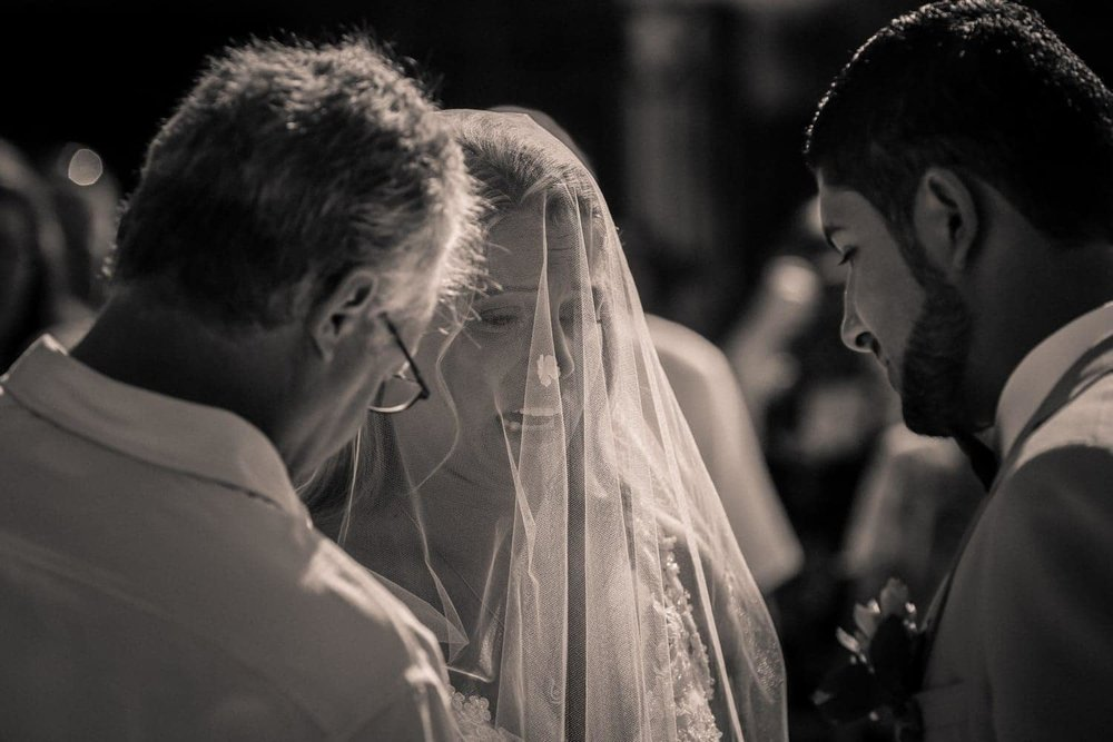 Emotional bride wearing white veil standing at altar at Villa Avalon in Costa Rica.