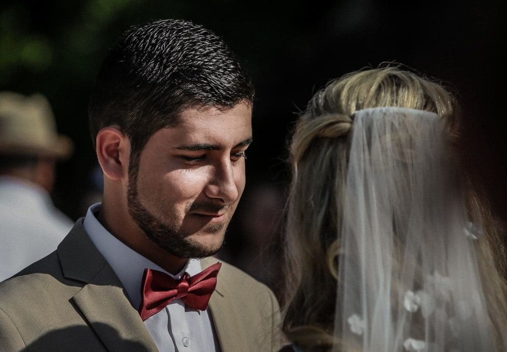 Groom wearing red bowtie looks at bride during wedding ceremony.