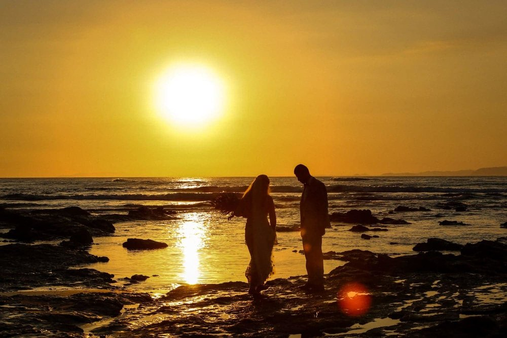 Sun sets in Punta Leona as bride and groom walk on rock on beach.