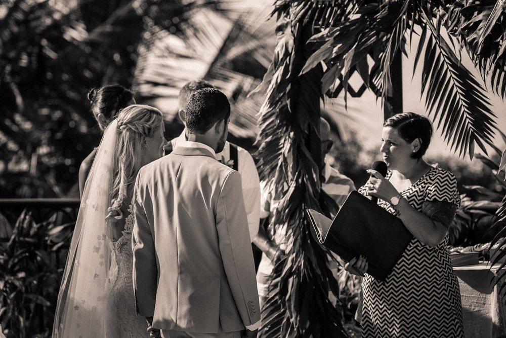 Officiant marries couple standing at arch decorated with exotic plants.