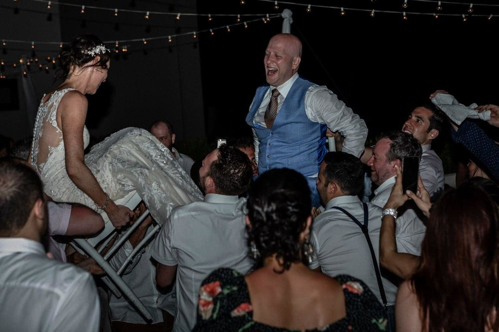 Photo of couple celebrating wedding during hora chair dance in Costa Rica.