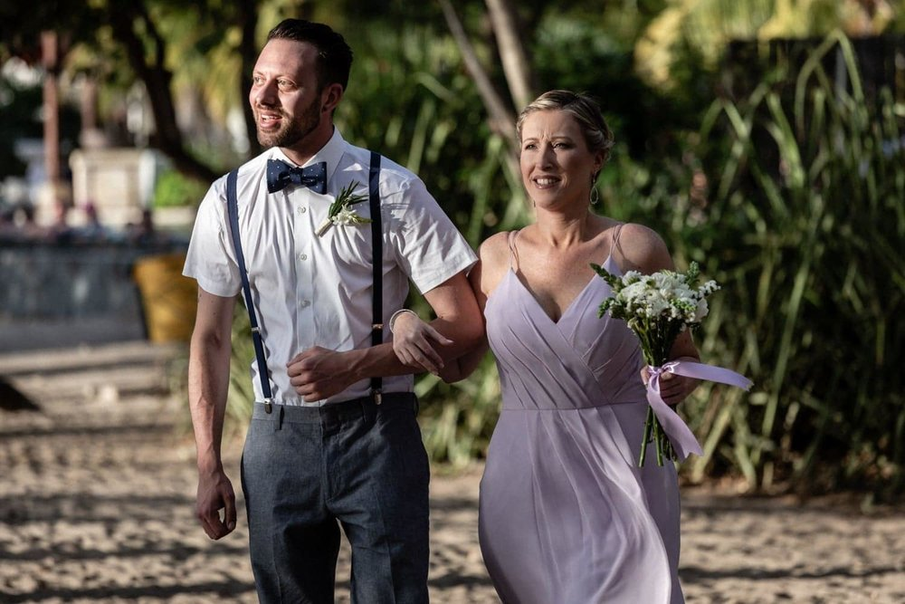 Bridesmaid and groomsman walk arm in arm to altar on beach.