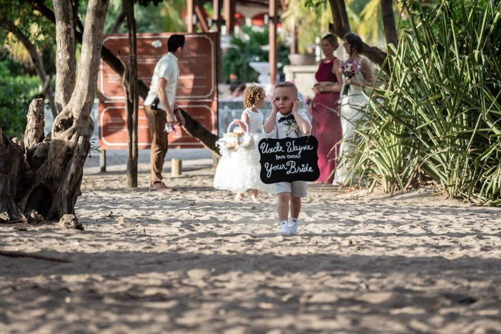 Ring bearer walking to altar on beach in Costa Rica.