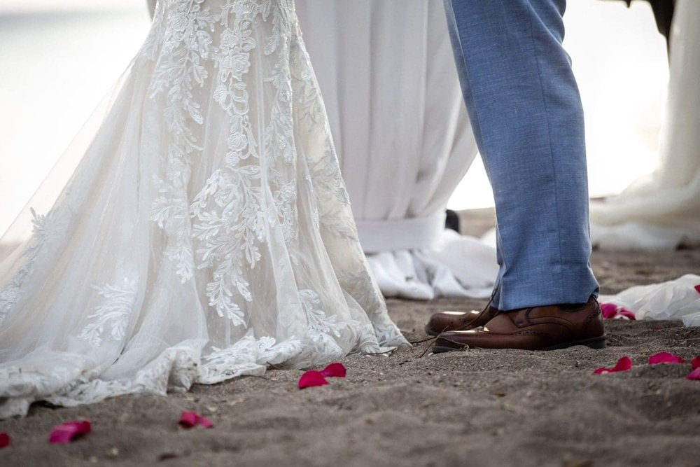 Rose petals decorate the sand and the base of the altar where bride and groom stand.