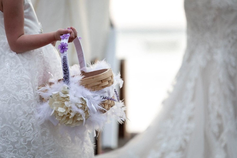 Flower girl stands at altar on beach holding basket with rose petals.