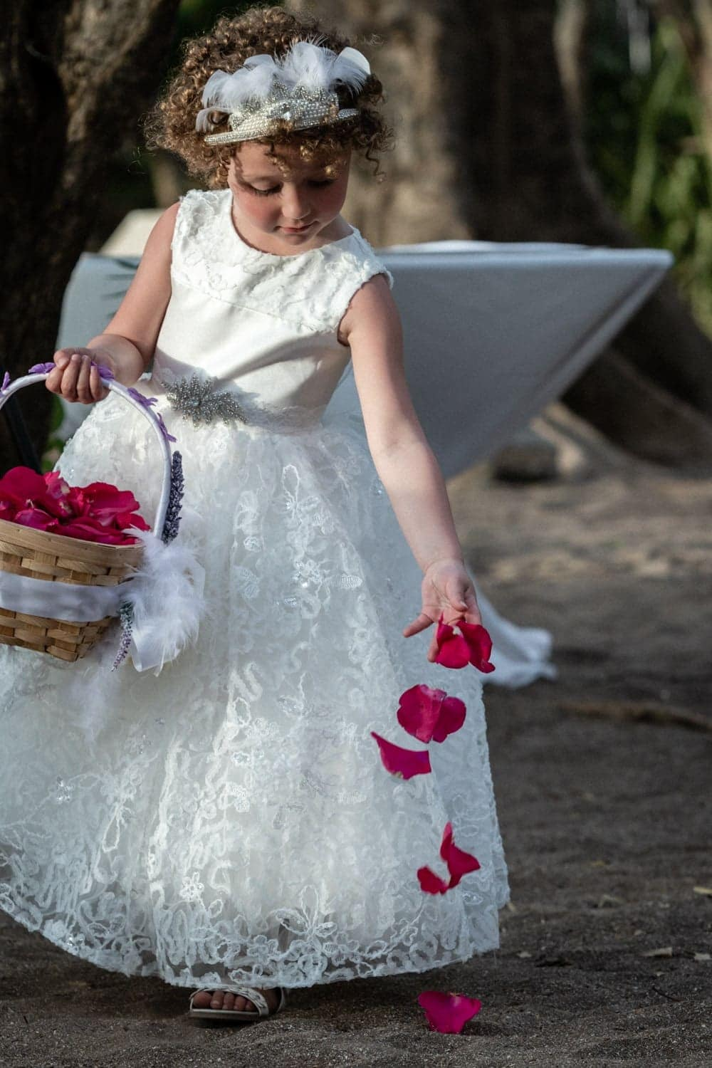 Flower girl tosses red rose petals on beach before bride walks to altar.