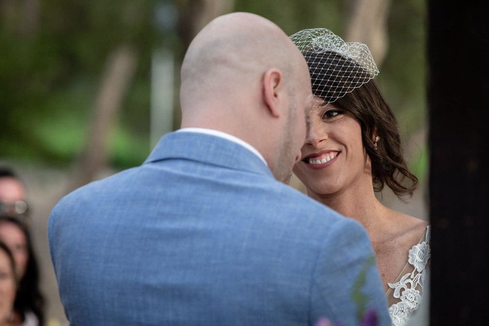 Smiling bride wearing birdcage veil looks at future husband.